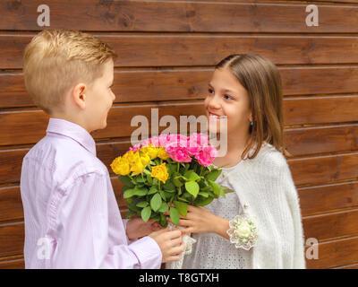 Cute little boy, Blumenstrauß charmante kleine Dame - lächelnde Mädchen in Liebe empfangen von Gelb und Rosa Rosen von Freund - Generation z - Stockfoto