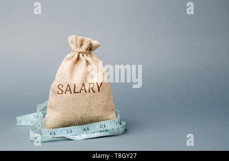 Geld beutel mit dem Wort Gehalt und Maßband. Lohnkürzungen. Das Konzept der begrenzten profitieren. Mangel an Geld und Armut. Kleine Einkommen. Gehaltskürzung.