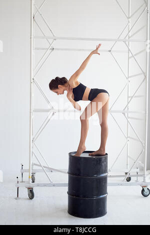 Anmutige gymnast steht auf einem hohen schwarz Barrel, macht komplexe Formen. Sport, Fitness, Stretching. - Stockfoto