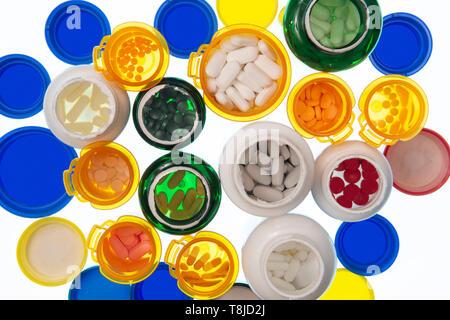 Horizontale abgeschossen, der eine große Gruppe in verschiedenen Größen und Farben der offenen Pille Flaschen mit Pillen gefüllt. Flaschen und Deckel sind auf einem hellen Tab - Stockfoto