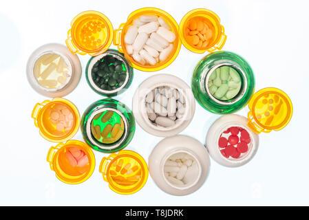 Horizontale abgeschossen, der eine große Gruppe in verschiedenen Größen und Farben der Pille Flaschen mit Pillen gefüllt. Flaschen nur. Kein Deckel. Auf einem Licht genommen - Stockfoto