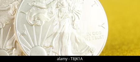 Nahaufnahme von Silber und Golden Eagle American Eagle eine Unze Münzen auf goldenem Hintergrund auf der linken Seite platziert - Stockfoto