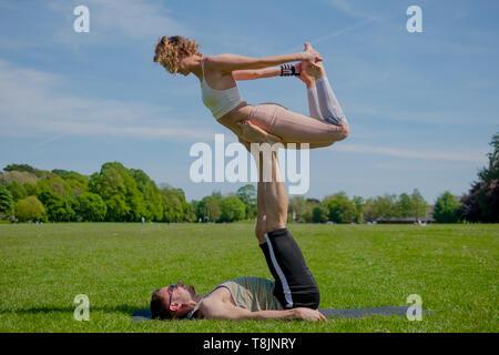 Junge athletische verliebtes Paar Durchführung acro Yoga im Roath Park auf einem hellen, sonnigen Tag. - Stockfoto