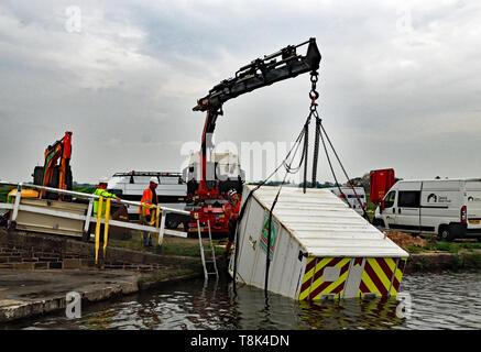 Ein Container ist aus dem Leeds und Liverpool Canal in der Nähe von haskayne nach einem Akt von Vandalismus mit JCB über Nacht am 23. April 2019 Cw 6702 angehoben - Stockfoto