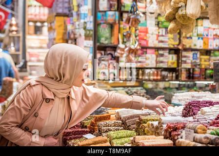 Schöne muslimische Frau in Kopftuch und modernen schaut auf traditionelle türkische Nachspeisen in Ägypten Basar in Eminonu, Istanbul, Türkei verkauft. - Stockfoto