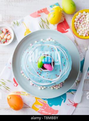 Ostern Kuchen mit bunten Eiern. Weiß Holz- Hintergrund. Ansicht von oben. - Stockfoto