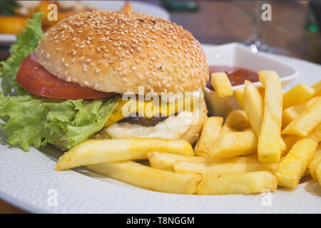 Double Cheeseburger mit Hackfleisch, Cheddar Käse, Tomaten, eingelegte Zwiebeln, Senf und Ketchup mit Pommes Frites und irisches Bier im Pub - Stockfoto