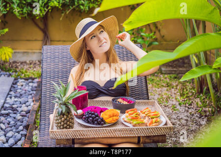 Junge Frau essen Frühstück in einem Sessel auf einem Tablett mit Obst, Brötchen, Avocado Sandwiches, smoothie Schüssel am Pool. Sommer gesunde Ernährung, vegan - Stockfoto