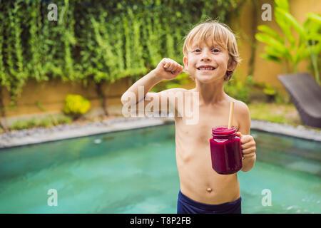 Cute boy Holding eine Flasche Dragon Fruit Smoothie oder Saft biegt seine Muskeln und lächelnd - Stockfoto