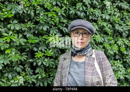 Modische taiwanesischen Frau der Chinesischen Ethnie gegen Hintergrund grün - Stockfoto