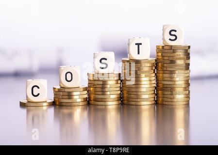 Steigende Stapel von Münzen mit dem Wort Kosten | Verwendung weltweit - Stockfoto