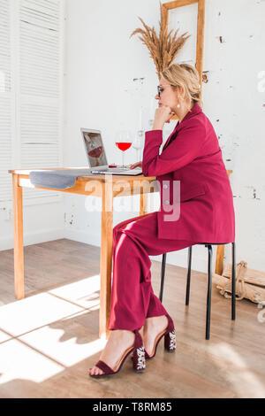 Seitenansicht des zuversichtlich weibliche Designer mit blonden Haaren Ernst am Bildschirm des Laptop suchen, Arbeiten am neuen Projekt, im Internet surfen. Volle Länge p - Stockfoto