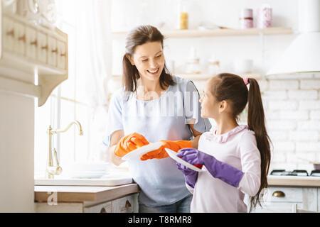 Helfende Hand. Nettes junges Mädchen ihrer Mutter helfen, den Abwasch in der Küche - Stockfoto