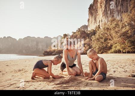 Lächelnde Mutter und ihren zwei entzückende Kinder im Sand spielen zusammen auf einem sonnigen Strand in den Sommerferien - Stockfoto