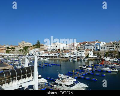 Blick auf den Kanal Hafen von Ciutadella de Menorca mit verschiedenen Boote im Vordergrund und im Hintergrund der blauen Himmel die Häuser und Denkmäler von - Stockfoto
