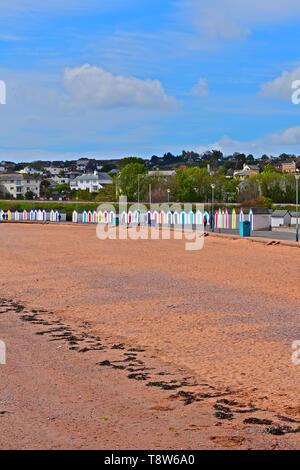 Mitte morgen Ansehen bei Ebbe an Goodrington Sands in der Nähe von Paignton. Mehrfarbige Strandhütten eine bunte Kulisse für die roten Sandstrand machen. - Stockfoto