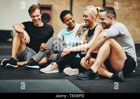 Gruppe von lächelnden Freunde in Sportkleidung reden, während er auf dem Gym, nach dem Training - Stockfoto