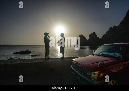 Kap Verde, Cabo Verde Archipel, Brava Insel: zwei Männer, die in der Nähe ein Auto und den Sonnenuntergang im Hintergrund, Dorf von Faja de Agua. Die meisten inhabi - Stockfoto