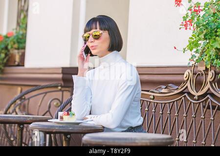Call Freund. Mädchen Mode Dame mit Smartphone. Freizeitaktivitäten Konzept. Frau attraktive Elegante brunette verbringen Freizeit Cafe Terrasse Hintergrund. Angenehme Zeit und Freizeit. Entspannen Sie sich und Kaffeepause.