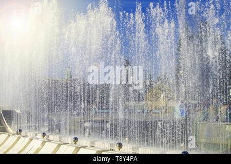 Stadt Springbrunnen und zufällige Menschen, durch Spritzer auf sonnigen Sommertag. - Stockfoto