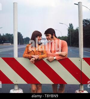 Das israelische Musikerpaar Esther & Abi Ofarim posiert in orangener Kleidung vor dem Brandenburger Tor; Deutschland 1967. Die israelischen Musiker paar Esther & Abi Ofarim posiert in orange Kleidung vor dem Brandenburger Tor; Deutschland 1967. - Stockfoto