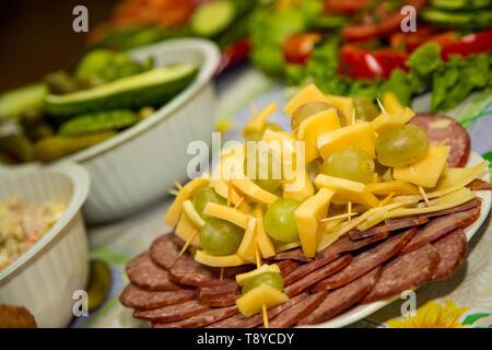 Andere Art von Wurst und Schinken sind in eine Platte mit Käse und Trauben gelegt. - Stockfoto