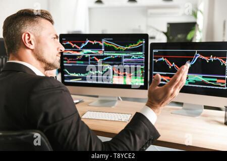 Bild von ernsthaften Geschäftsmann 30 s tragen Anzug arbeiten im Büro und suchen auf dem Computer mit Grafiken und Diagramme am Bildschirm - Stockfoto