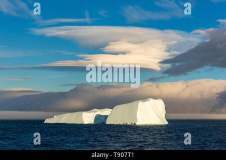 Eine spektakuläre eckig Eisberg aufgeteilt in zwei Hälften schwimmt unter einem Linsenförmigen Wolke von Elephant Island im Südlichen Ozean - Stockfoto