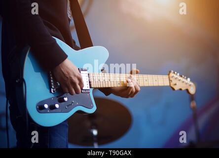 Ein Mann in einem schwarzen Pullover in Blue Jeans spielt eine blaue, elektrische Gitarre, durch Sonnenlicht beleuchtet, auf blauem Hintergrund. - Stockfoto