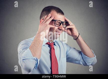 Junge Geschäftsmann in der Frustration Tempel reiben und halb geschlossenen Augen auf grauem Hintergrund. - Stockfoto