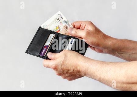 Nahaufnahmen der Hände des Menschen unter 10 lbs und 20 lbs Hinweis von einem schwarzen Lederetui, auch mit Kreditkarten - Stockfoto