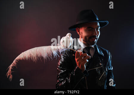 Männliche Magier mit weisse Taube auf dunklem Hintergrund - Stockfoto