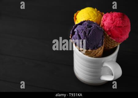Waffeln mit leckeren Eis Farbe Creme in Schale auf Holztisch - Stockfoto