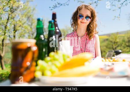 Jugendlich im Alter von Mädchen in rot kariertem Hemd sitzt von Tabelle auf Geburtstag Gartenparty - Nahrung und Flaschen auf dem Tisch-sonnigen Tag - Stockfoto