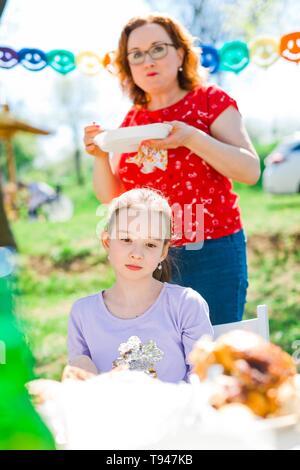 Traurig jugendlich im Alter von Mädchen dunkel Sitzen durch Tabelle auf Geburtstag Gartenparty, Mutter hinter Essen - sonnigen Tag - Stockfoto