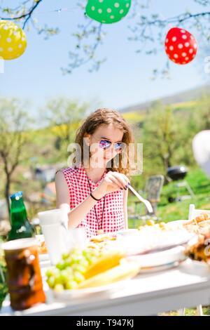 Jugendlich im Alter von Mädchen in rot kariertem Hemd sitzt von Tabelle auf Geburtstag Gartenparty Essen mit Kunststoff Gabel - Stockfoto