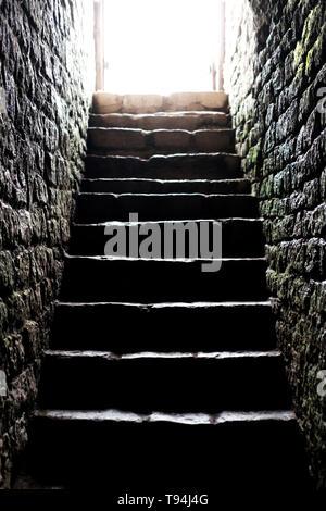 Starke Sonne leuchtet am Eingang zum Keller. Steintreppe in die Krypta. Leben nach dem Tod Konzept - Stockfoto