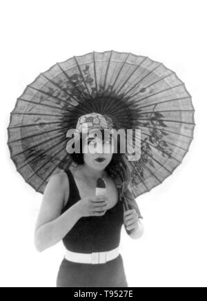 """Titel: """"Betty Compson mit Sonnenschirm, in Badehose, Blick leicht nach rechts, essen Eskimo Pie."""" Betty Compson (März 19, 1897 - April 18, 1974) war ein US-amerikanischer Schauspieler und Filmproduzent. Die meisten berühmten in Stummfilmen und frühen Tonfilms, ist sie am besten in ihre Performances in den Docks von New York und von Barker, Letztere verdienen eine Nominierung für den Academy Award für die beste Schauspielerin bekannt. Ihre Popularität erlaubte ihr kreative Kontrolle über Ihre Filme zu haben, wie sie auch in der Lage war, zu produzieren."""