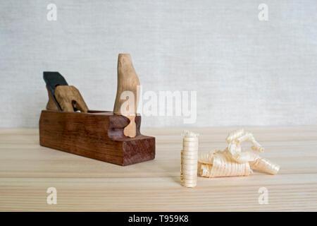 Späne nach dem Hobeln von Holz Esche auf dem Hintergrund der Ebene schließen oben. DIY-Konzept. Holzbearbeitung und Handwerk Werkzeuge. Zimmerei Handwerkzeuge. Holz- Bac - Stockfoto