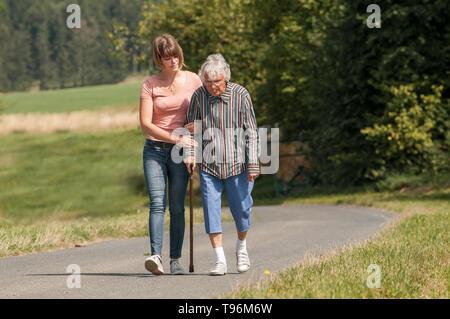 Junge Frau helfen älteren Dame mit Stock - Stockfoto