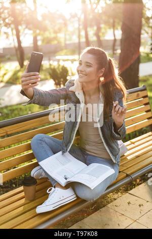 Lächelnde junge Frau trägt Jacke sitzen auf einer Bank im Park, lesen Magazin, selfie - Stockfoto