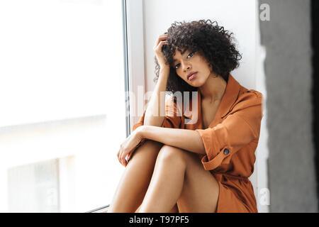 Geheimnis ziemlich afrikanische Frau in die Kamera schaut beim Sitzen in der Nähe der Fenster - Stockfoto