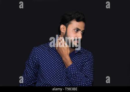 Porträt eines jungen Mannes Modell seinen Hals berühren mit der Hand in Schwarz isoliert Hintergrund - Stockfoto