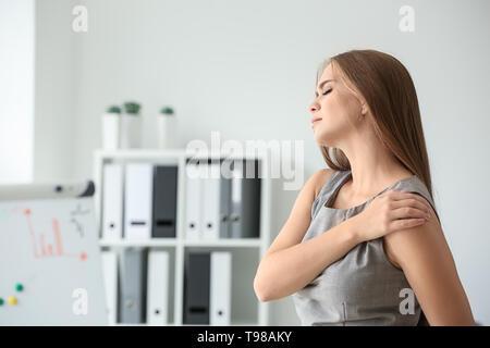 Junge Frau mit Schmerzen in der Schulter am Arbeitsplatz - Stockfoto