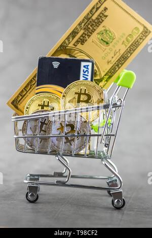 Blick auf Metall bitcoins und VISA Kreditkarten und Amerikanische Dollar Banknoten im Einkaufswagen. Konzept Bild für cryptocurrency - Stockfoto