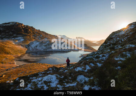 Wanderer schaut über die schneebedeckten Berge und Seen der Lofoten, Lofoten, Nordland, Norwegen - Stockfoto
