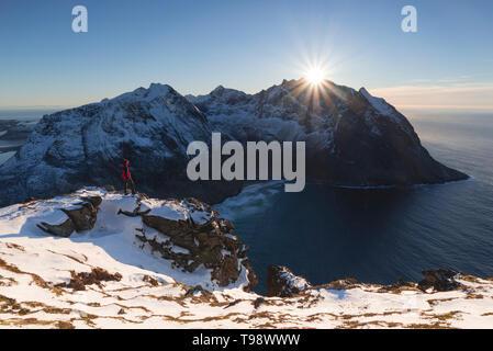 Wanderer Gesichter der Sonne, kurz bevor es verschwindet hinter dem Gipfel des Kjerringa, Ryten, Lofoten, Nordland, Norwegen - Stockfoto