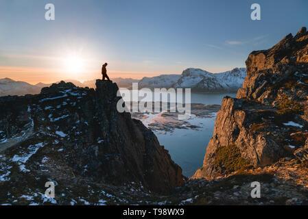 Wanderer bei Hoven im Gegenlicht sieht in den Abgrund und auf die umliegende Landschaft, Hoven, Lofoten, Nordland, Norwegen - Stockfoto