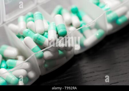 Extreme Nahaufnahme von sieben Tag Pille Box mit Pillen. Blu Pillendose mit Dienstag Pillen sichtbar. Öffnen Pillenschachtel auf schwarzem Hintergrund - Stockfoto