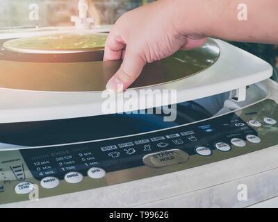 Mann öffnen Sie die Waschmaschine Tür, er Wäsche - Stockfoto